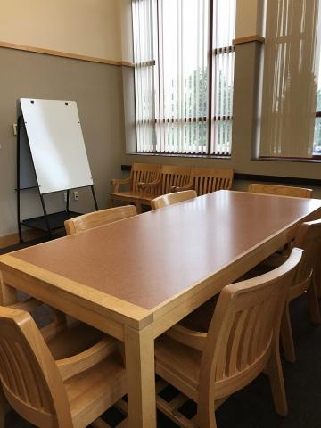 Study Room B with rectangular table, 6 chairs at the table, white board, and three chairs lined against the wall